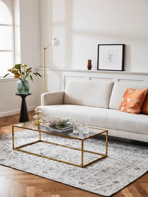 petit salon avec tapis vintage, table basse dorée et en verre, petit canapé beige et coussin terracotta