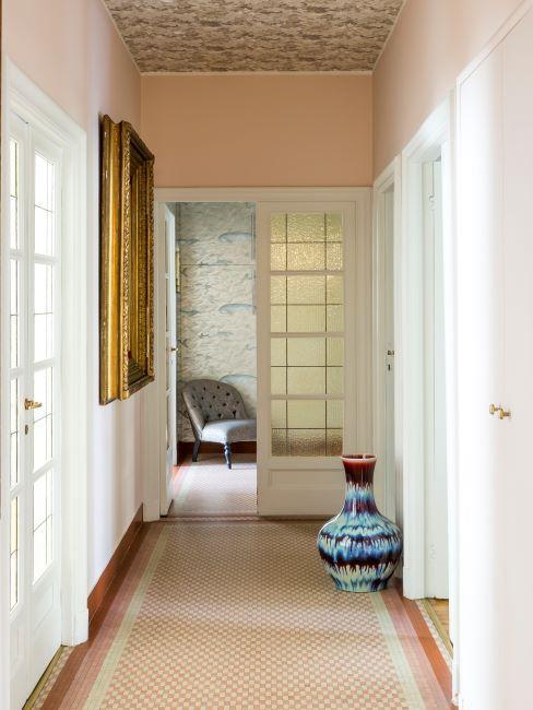 couloir couleur pêche, portes blanches style classique, vase décoratif