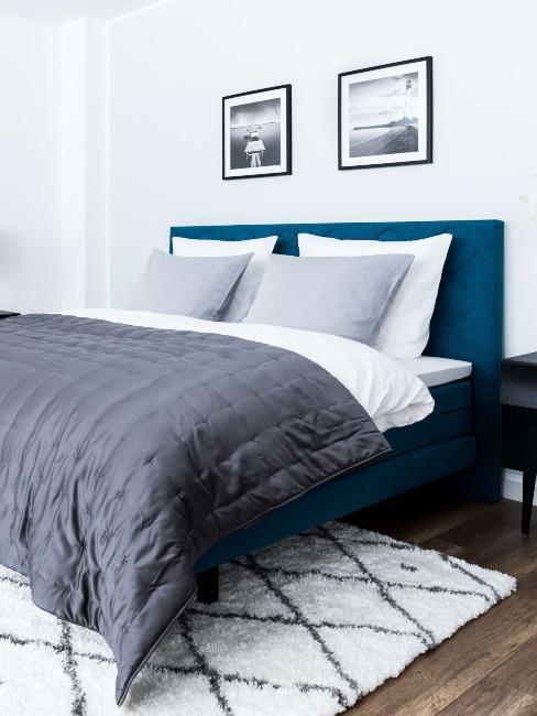 Lit boxspring avec tête de lit bleu, et tapis berbère