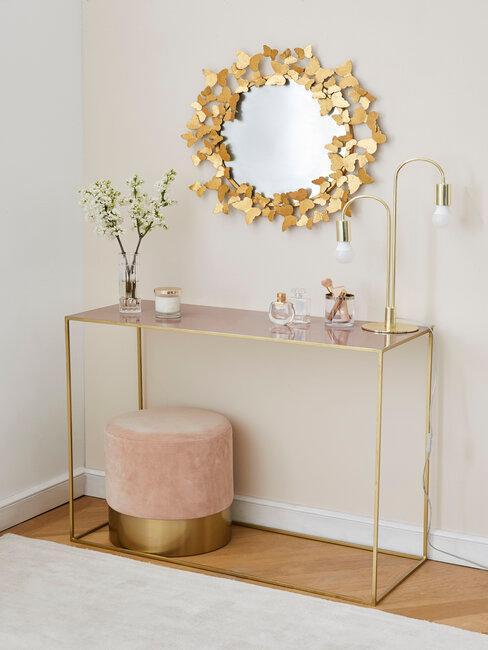 miroir doré au-dessus d'une console et d'un pouf rose