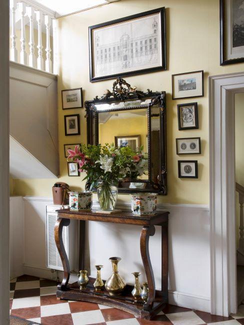 console en bois, miroir mural avec cadre en bois massif, cadre décoratif, cadres photo sur le mur, vases dorés, mur jaune et blanc cassé