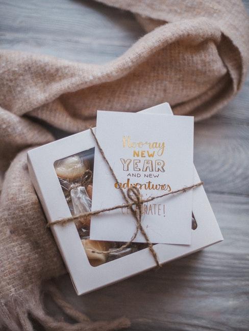 Plaid cosy rose et boîte blanche avec cadeaux et vœux de nouvel an