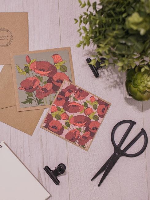 Paire de ciseaux noirs, plante verte et cartes de vœux florales