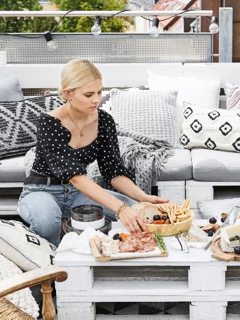 Femme sur terrasse style boho, meubles diy en palette