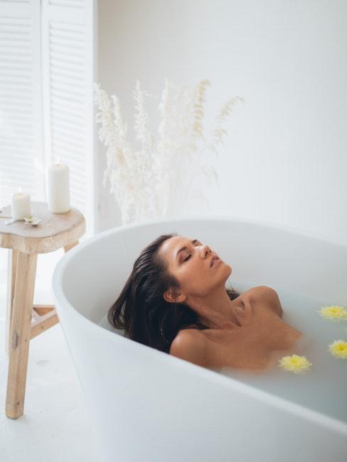 salle de bain minimaliste, table d'appoint naturelle en bois massif, femme en train de prendre un bain relaxant