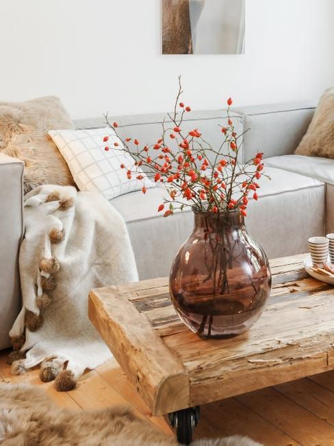 salon style rustique avec canapé gris, coussin déco divers, vase en verrre teinté et table basse en palette