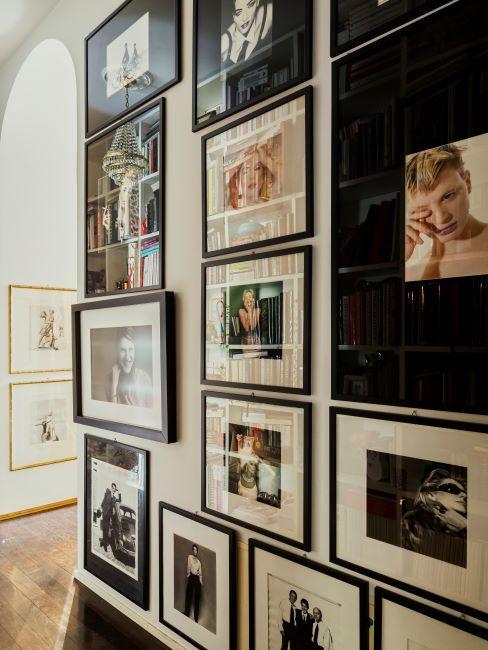 photos de famille dans de cadres noirs sur un mur de couloir beige