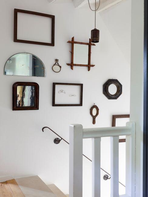 cage d'escalier blanc avec sélection de photos et miroirs sur le mur