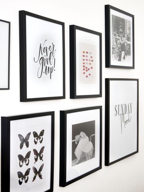 couloir blanc décoré de divers cadres noirs avec photos et images