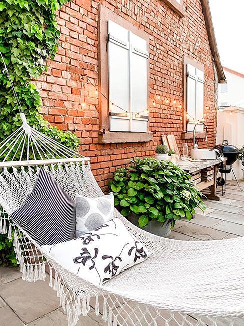 hamac blanc style boho avec coussins sur une terrasse extérieure