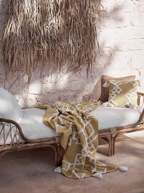 lit extérieur en rotin avec plaid jaune boho