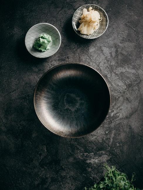 table en marbre, vaisselle en céramique noire, wasabi et gingembre