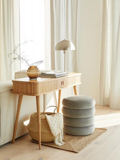 bureau en bois avec pouf en velours, lampe de table doré et panier en osier
