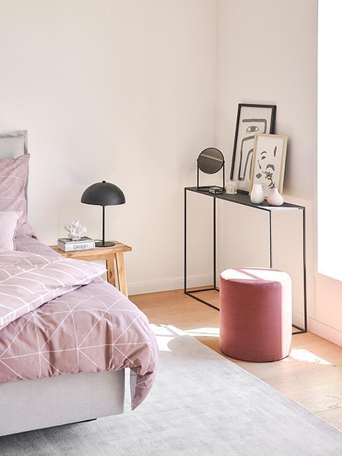 chambre avec console noire, cadres, pouf rose