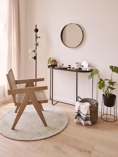 console noir en métal avec miroir rond et chaise en bois et cannage