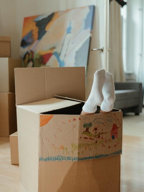 enfant caché dans une boîte en carton coloriée