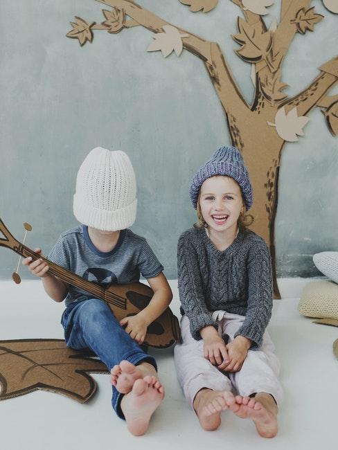 Deux enfants jouant dans une forêt en carton avec une guitare en carton