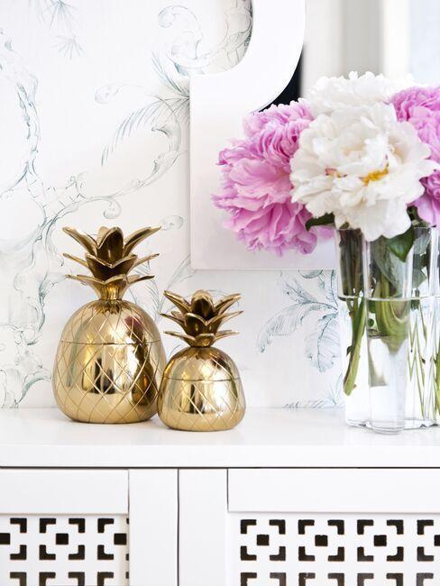 console avec bouquet des pivoines dans un vase transparent, boîtes décoratives ananas dorées