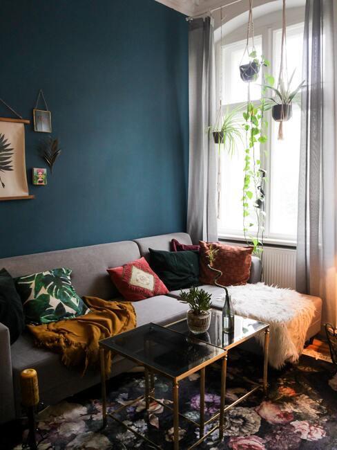 petit salon avec mur de couleur vert sauvage et fauteuil d'angle avec coussins colorés et plantes suspendues