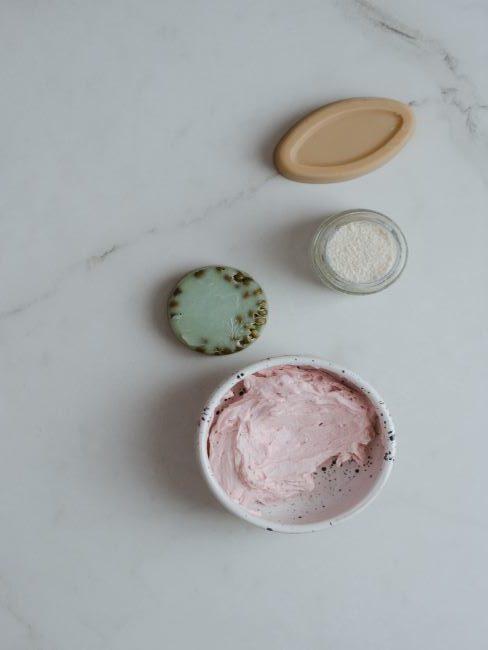 masque visage DIY rose dans un récipient blanc et divers savons