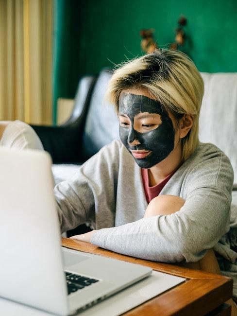femme avec masque ay charbon sur le visage pendant le télétravail