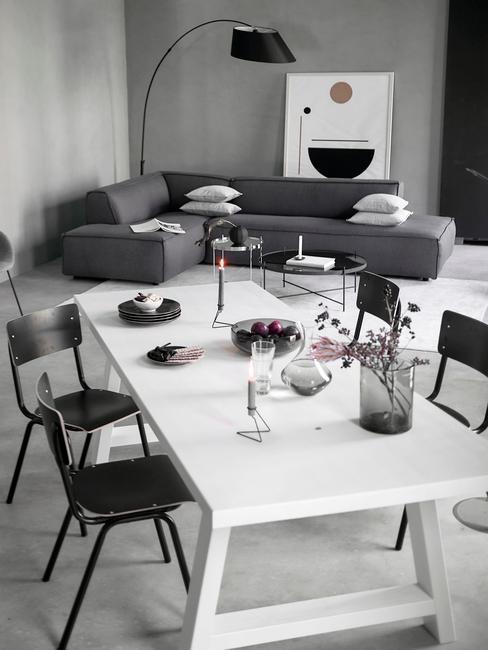 Salle à manger et salon moderne et design épuré avec table blanche, chaises noires et fauteuil gris