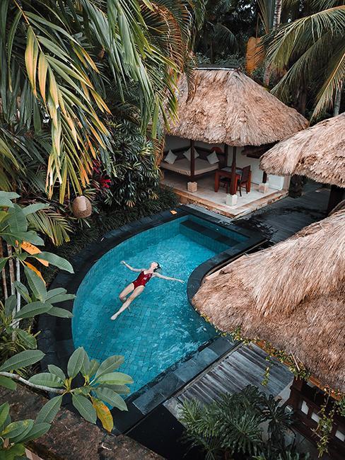 Femme entrain de se baigner dans une piscine dans un lieu exotique