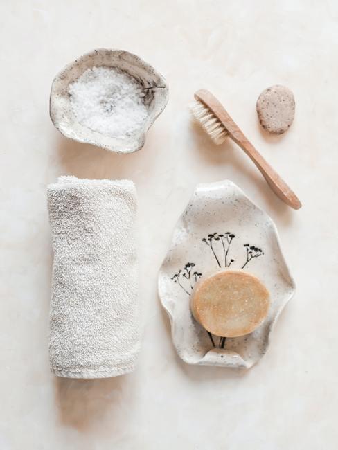 serviette de bains blanche, savon, brosses et sel pour gommage
