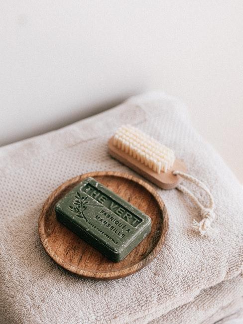 Savon vert sur assiette en bois, brosse de gommage et serviettes de bains crème