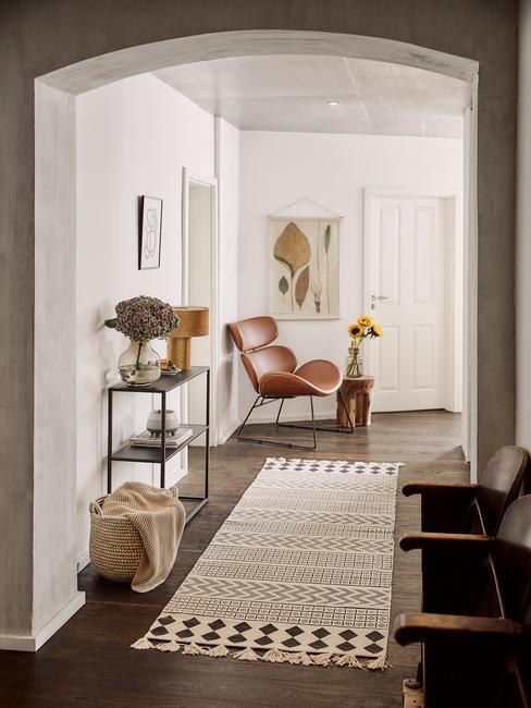 Couloir avec tapis rectangulaire fauteuil en cuir et décoration
