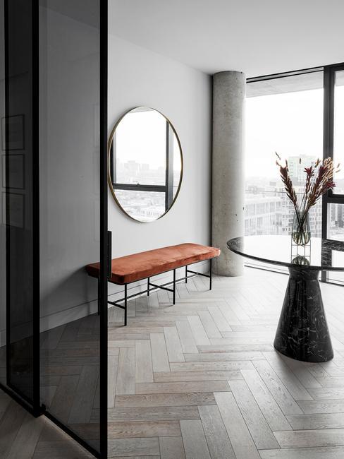 Grand ouloir avec miroir rond, banquette orange et table ronde