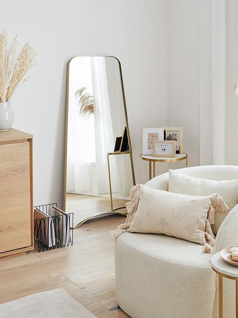 Grand miroir doré posé au sol dans un salon boho avec fauteuil beige et herbe de la pampa