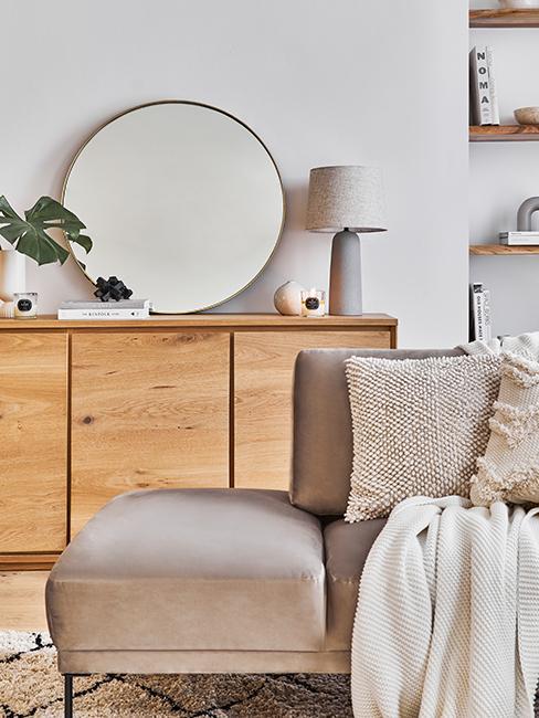 miroir rond posé sur un buffet en bois avec un canapé beige