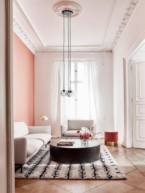 Salon avec mur rose et moulures au plafond
