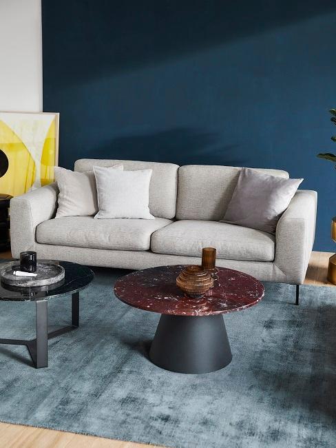 Salon avec peinture murale bleu foncé, tapis bleu doux et canapé gris