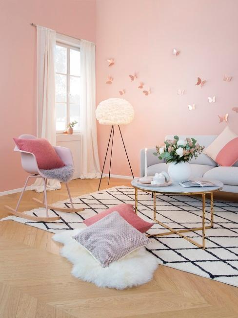 Salon aux murs roses et canapé gris, grand tapis à motifs