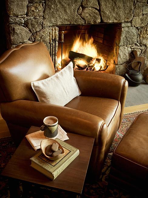 coin cosy avec fauteuil brun en cuir au coin de la cheminée