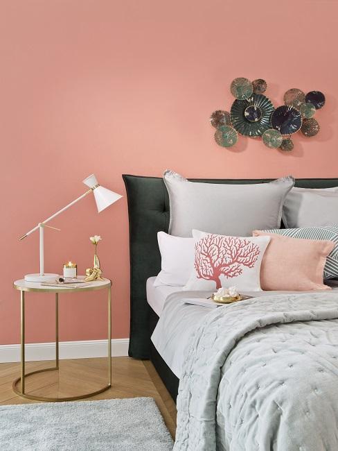 chambre avec mur rose, lit avec linge de lit gris et table de chevet ronnde