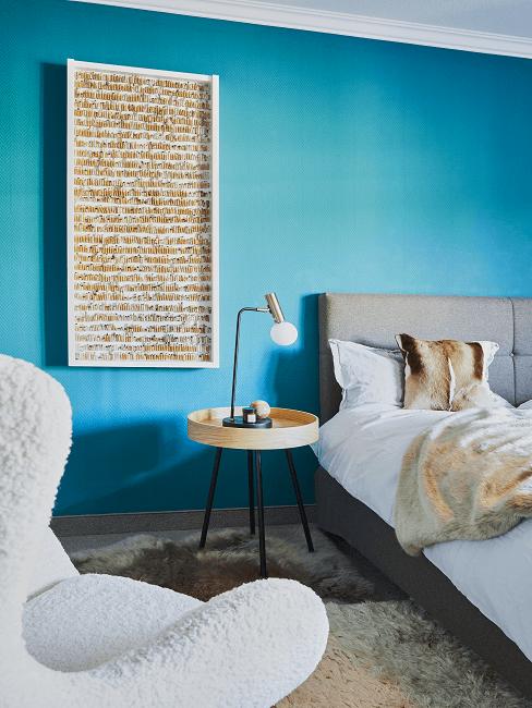 chambre avec mur bleu et cadre au mur. fauteuil moelleux blanc et lit gris