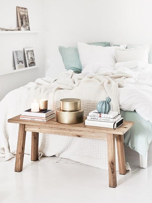 chambre blanche avec accents vert pastel, banc en bois, bout de lit en bois, lit défait,