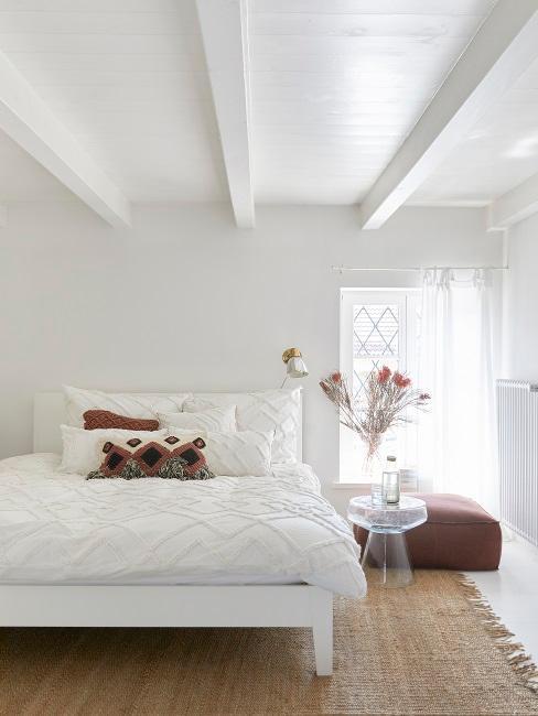 chambre au grenier, chambre blanche avec accents rouge ou brun, poutres au plafond, coussin de sol