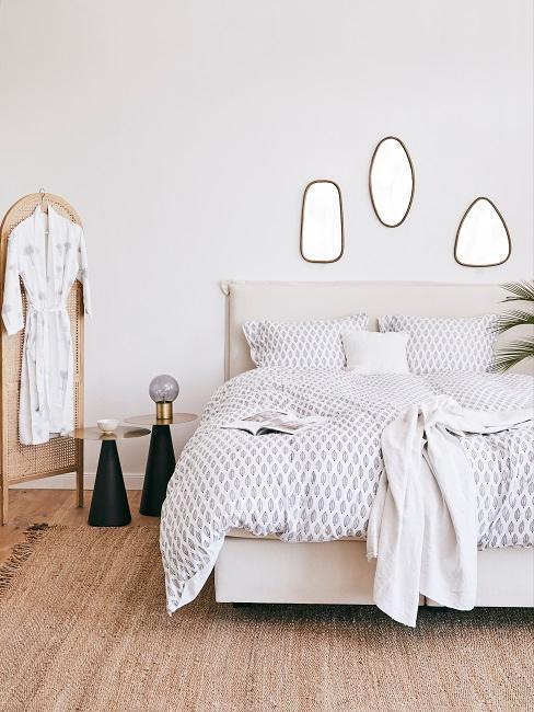 chambre blanche avec paravant en bois, gros plaid blanc, miroir mural en lot de trois,