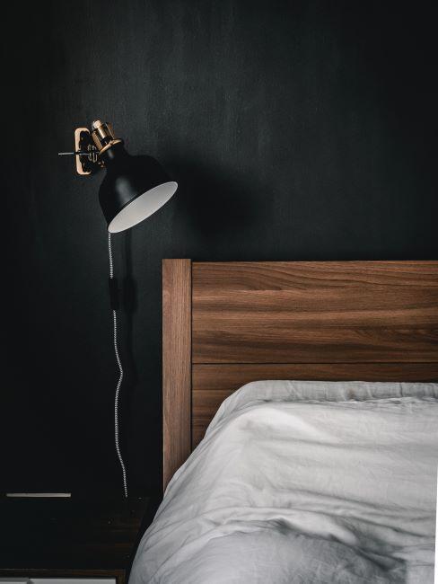 zoom sur lit en bois dans une chambre à coucher aux murs anthracite et lampe de chevet moderne