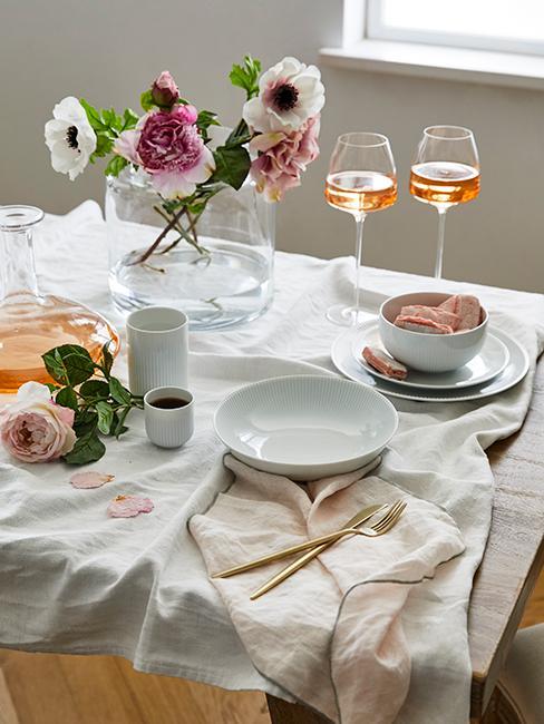 Table romantique avec assiette blanche, couuverts dorés, verres de vin et bouquet de fleurs