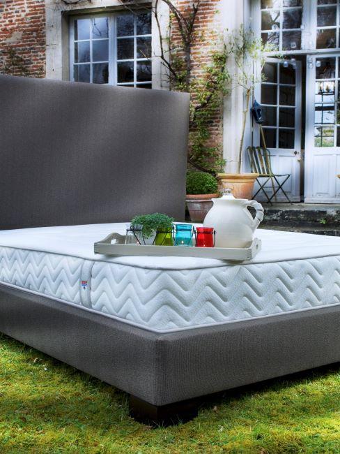 lit matelas tapissier avec un plateau posé dessis, lit situé sur la pelouse devant une maison