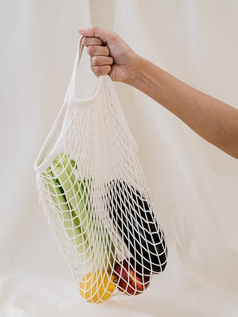 filet de course avec légumes tenu par une main