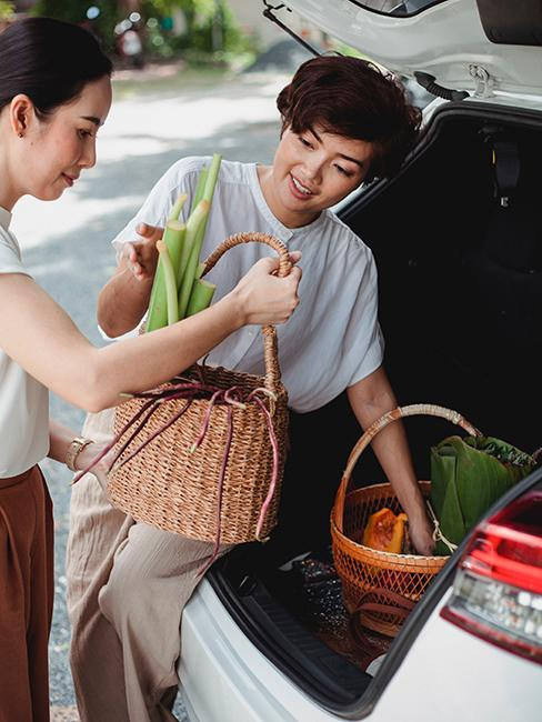 deux femmes entrain de mettre leurs courses dans la voiture