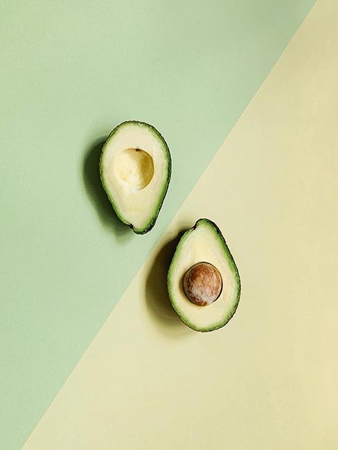 Avocat coupé en deux sous fond jaune et vert