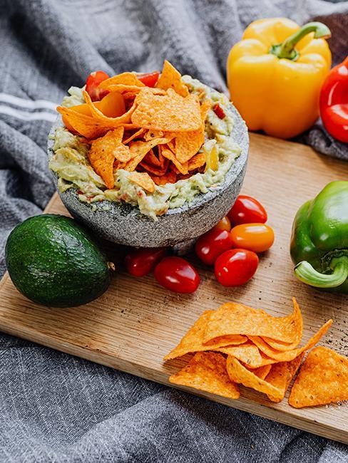 Plat de nachos avec guacamole maison posé sur une planche en bois