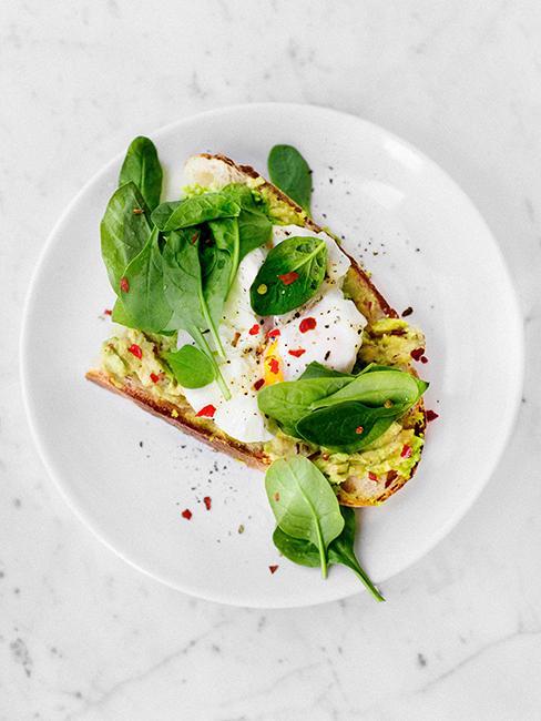avocado toast avec oeuf poché dans une assiette blanche
